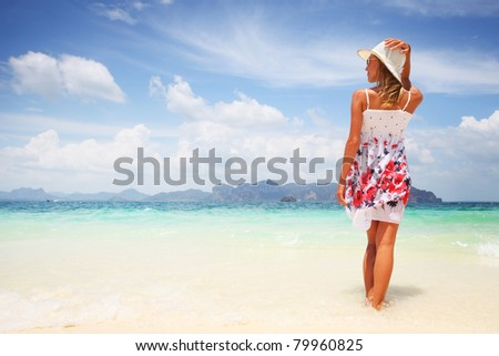 Woman in summer dress standing on wet sand by tropical sea - stock photo