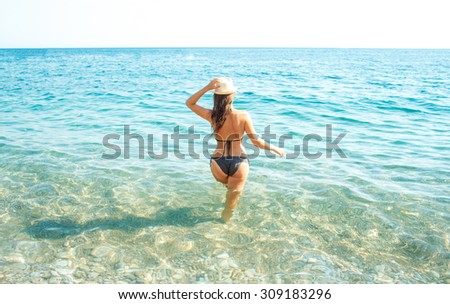 Woman in sun hat and bikini standing with her arm raised to her head enjoying looking view of beach on hot summer day - stock photo