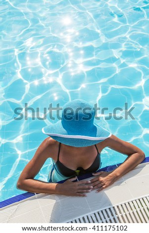 Woman in sun hat in the swimming pool. Top view. - stock photo