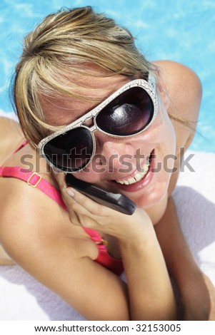 Woman in sunglasses besides a bright blue swimming pool talking into her mobile phone - stock photo