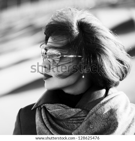 Woman in sunglasses looking away - stock photo
