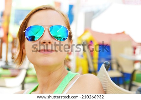 woman in sunglasses sitting at  cafe table - stock photo