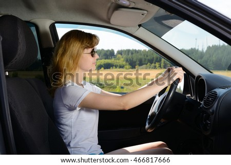 Woman in sunglasses sitting in the car