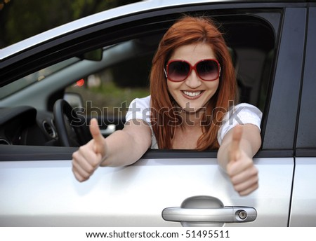 Woman in sunglasses smiling from her car to camera - stock photo