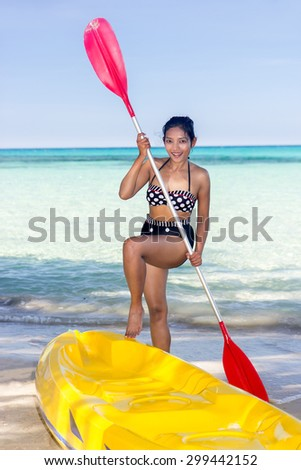 woman in swimsuit standing on the beach with paddle in her hand - stock photo