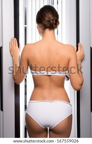 Woman in tanning booth. Rear view of beautiful young woman standing in tanning booth - stock photo