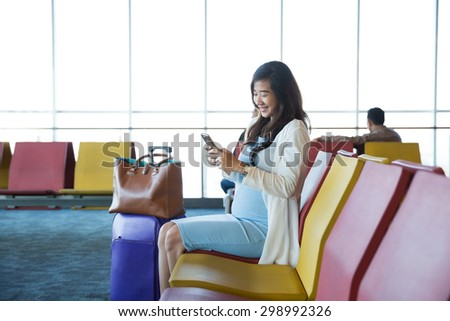 Woman in the airport lounge sitting in chair by the window and using a mobile phone for checking her flight details with wifi connection - stock photo