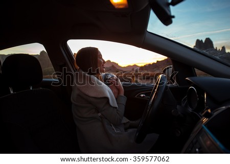 Woman in the car enjoying sunset