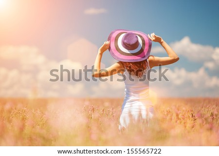 Woman in the field with flowers - stock photo