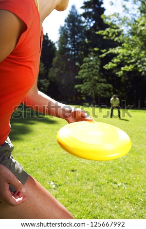 woman in the foreground about to throw a Frisbee disc to a man squatting in the background, grass and line of trees visible in the background - stock photo