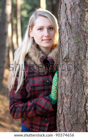 woman in the forest standing by pine tree