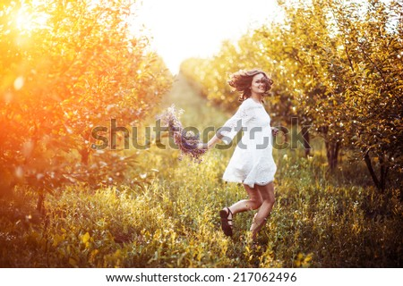 woman in the garden with a wreath on his head at sunset - stock photo