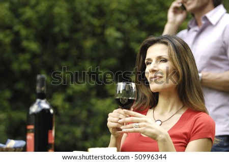 Woman in the garden  with wine - stock photo