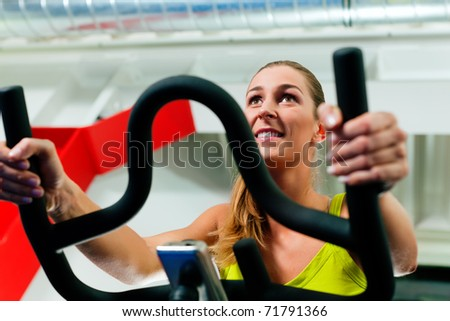 Woman in the gym, exercising their legs doing cardio training on bicycle - stock photo