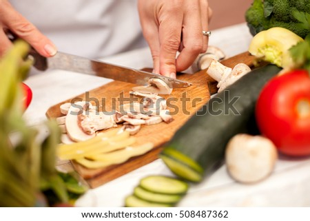 Woman in the kitchen cutting champignons on chopping board