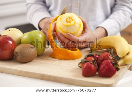 Woman in the kitchen peeling fruits - stock photo