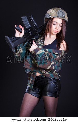 Woman in the military uniform with an assault rifle over black background - stock photo
