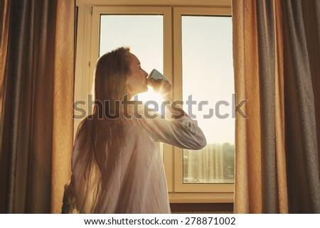 Woman in the morning. Attractive sexy woman with neat body is drinking hot tea or coffee from her cup and looking at the sunrise standing near the window in her home and having a perfect cozy morning. - stock photo