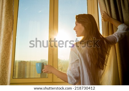 Woman in the morning. Attractive sexy woman with neat body is holding a cup with hot tea or coffee and looking at the sunrise standing near the window in her home and having a perfect cozy morning. - stock photo
