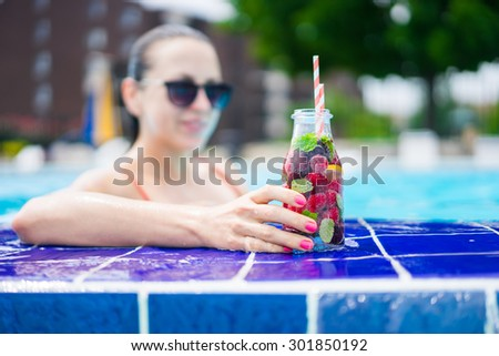Woman in the pool with detox water cocktail