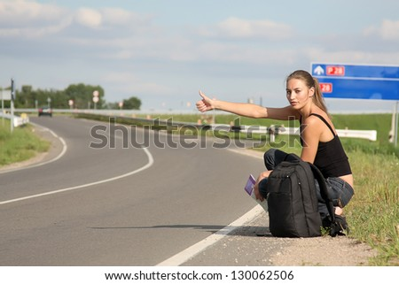 woman in the road auto-stop under the blue sky - stock photo