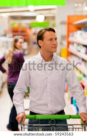 Woman in the supermarket looking after a guy she just met shopping there, she is ready to flirt a bit - stock photo