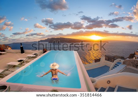 Woman in the swimming pool against sunset in Oia village on Santorini island, Greece - stock photo