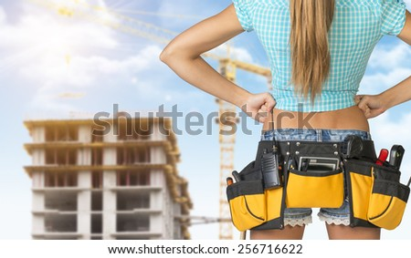 Woman in tool belt with different tools standing backwards, akimbo. Cropped image. Building under construction in background - stock photo