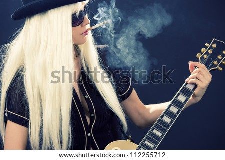 woman in top hat with golden electric guitar and cigarette