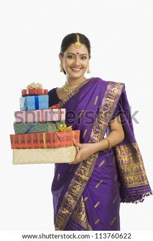 Woman in traditional Assamese dress holding gifts and smiling - stock photo