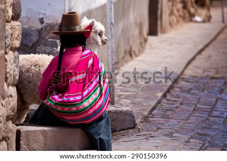 Woman in traditional clothes with lama sitting on stone in Cuzco - Peru - stock photo