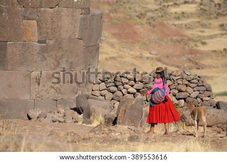 Woman in traditional clothes with lama sitting on stone in Puno - Peru. - stock photo