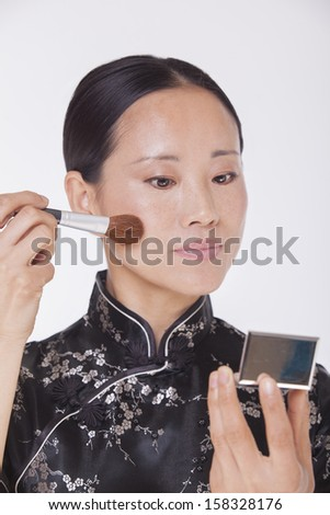 Woman in traditional clothing looking into a mirror and applying make up  - stock photo