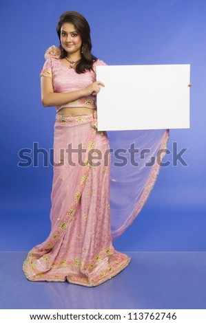 Woman in traditional dress and holding a blank placard - stock photo