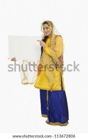 Woman in traditional Punjabi dress holding a placard - stock photo
