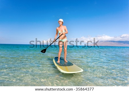 woman in tropical waters of hawaii with green stand up paddle board doing sport exercise relaxing