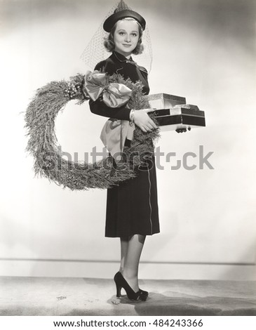 Woman in veiled hat carrying wreath and Christmas presents