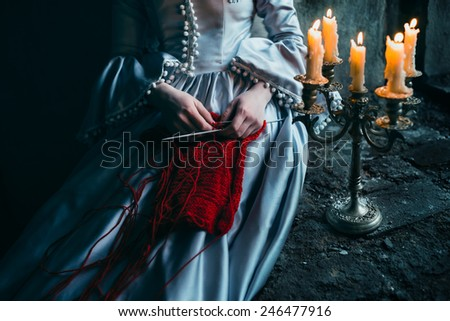 Woman in victorian dress imprisoned in a dungeon - stock photo