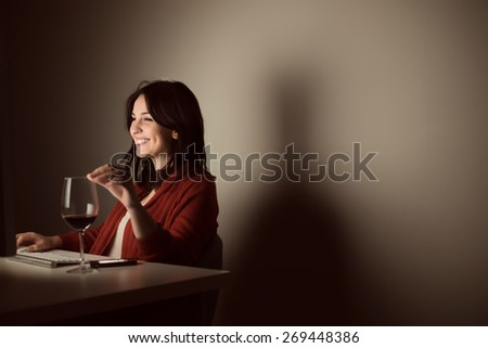 Woman in video call with a glass of wine on desk