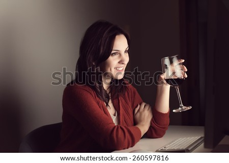 Woman in video call with a glass of wine on hand