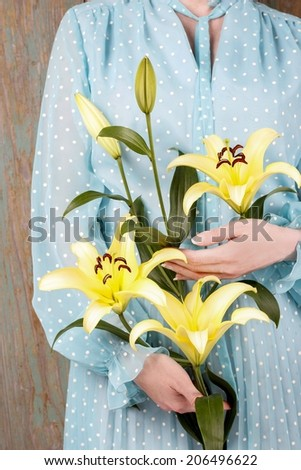 Woman in vintage blue dress holding yellow lily flower - stock photo