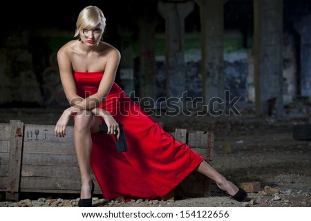 Woman in vintage look sitting on military box in old fabric ruins