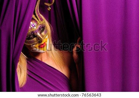 Woman in violet mask posing near curtain - stock photo