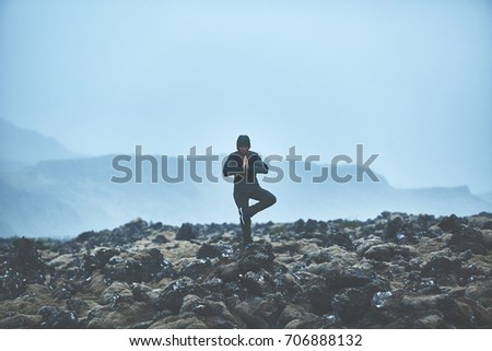 Woman in waterproof clothing stands in yoga pose on volcanic Lava fields on background of mountains of Iceland.