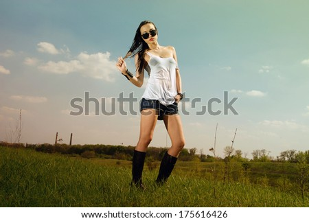 Woman in wet t-shirt, jeans and high boots standing on the field