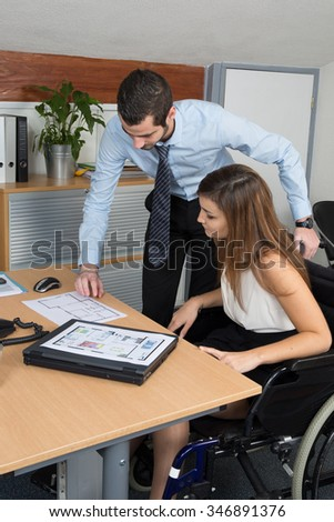Woman in wheelchair and a male colleague working in the office