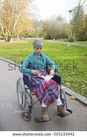 Woman in wheelchair reading a book in the park