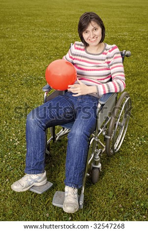 Woman in wheelchair with a red ball in hands - stock photo