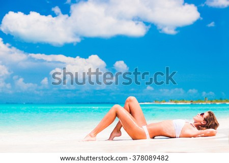 woman in white bikini  lying on tropical beach