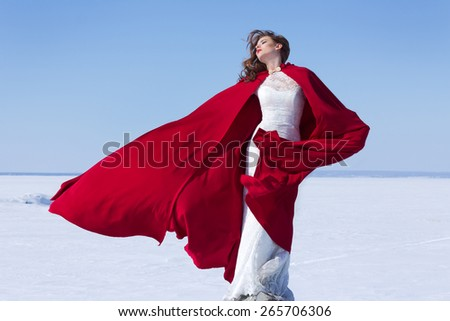 Woman in white bride dress with flying red fabric. Winter background - stock photo